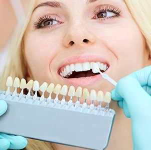woman comparing tooth to veneer