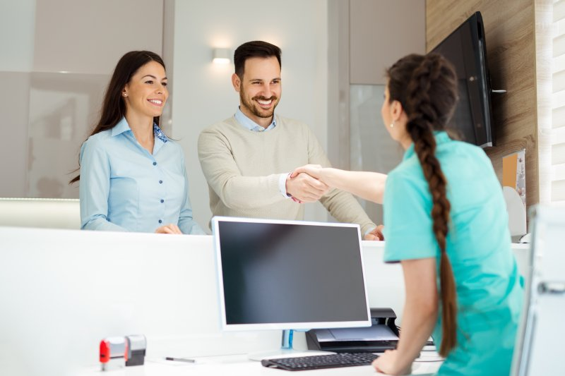 a couple shaking hands with a dental receptionist