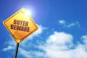 Buyer beware sign, indicating dangers of getting dental implants for cheap