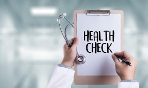 """Health check"" written on clipboard held in doctor's hands"
