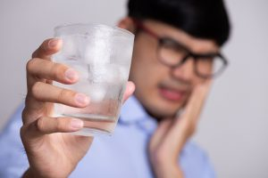 Man experiencing tooth pain after chewing on ice