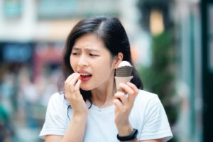 Woman eating ice cream, in pain because of sensitive teeth