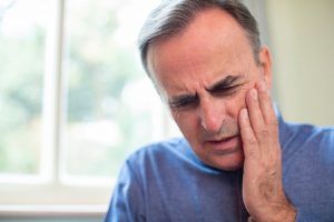 middle-aged man in blue shirt suffering toothache pain