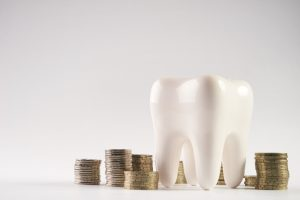 tooth model next to stacked coins against light background