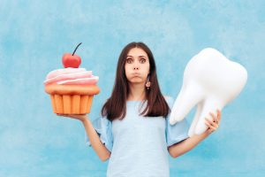 woman holding giant cupcake and tooth